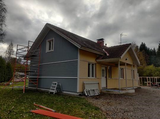 Talon maalaustyöt keskeneräisenä, päädyssä jo uusi maali.